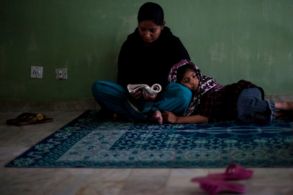 A Pakistani child rests while her mother reads at the Dastak women's shelter in Lahore on March 2, 2013.