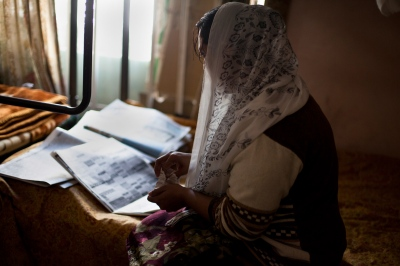 A Pakistani resident reads through employment advertisements in a newspaper at the Dastak women's shelter in Lahore on March 3, 2013.
