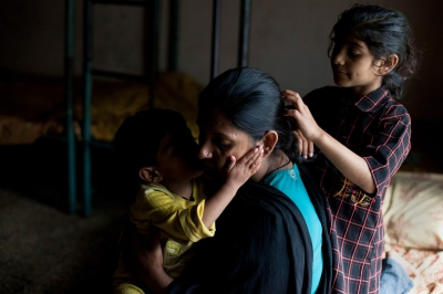 A Pakistani resident sits with her children in their bedroom at the Dastak women's shelter in Lahore on March 3, 2013.