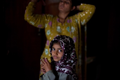 Pakistani child stands in front of her mother as she brushes her hair in their bedroom at the Dastak women's shelter in Lahore on March 4, 2013.