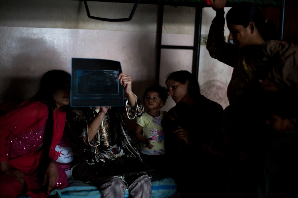 Pakistani Dastak resident Saira (2L), 43, holds up an x-ray of her injuries taken after a beating by her husband to show other residents at the Dastak women's shelter in Lahore on March 5, 2013.