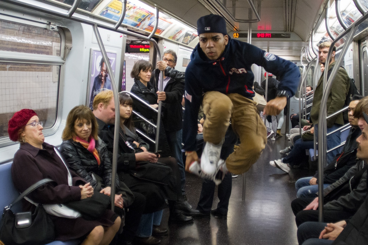 Randy, a member of the dancing crew W.A.F.F.L.E., does tricks on the subway in New York, November 2013.
