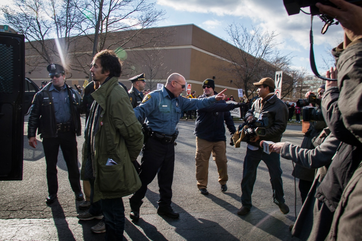 A policeman asks a journalist to stay away as he is putting a handcuffed protester into the car, Secaucus, New Jersey, November 2013.