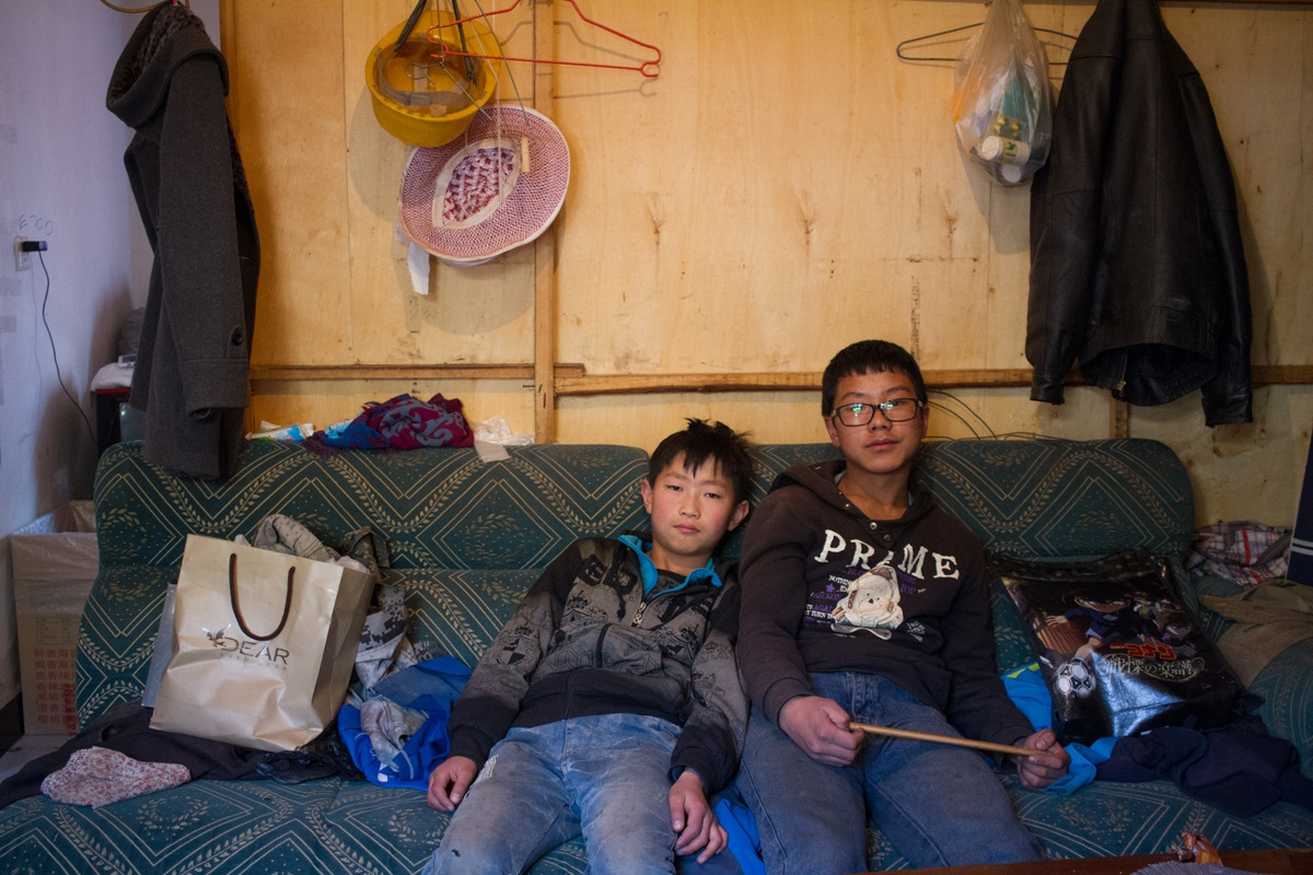 Li Nan and Li Jin, both come from their home village to Kunming to visit their parents during winter break, sit on the couch in their parents' room, February 2015.