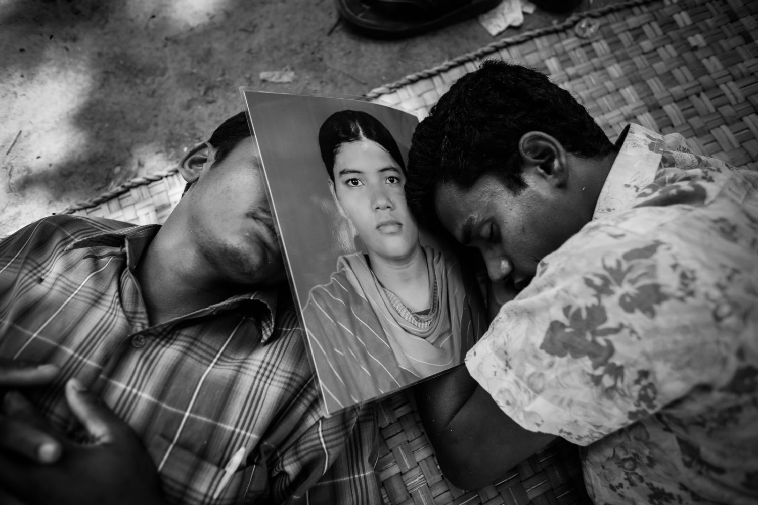 Two men sleep as they wait for news on their relative, a garment worker who is still missing after the collapse of the Rana Plaza building, in Savar, outside Dhaka.