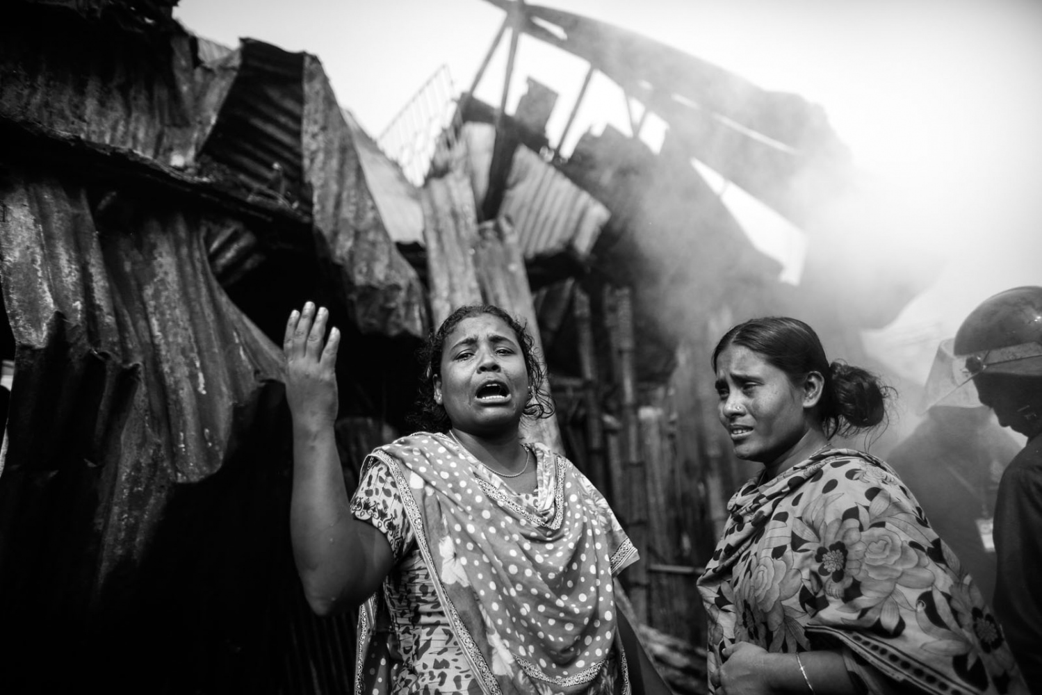 Garment workers cry after she lost all of her belongings in a fire at a slum at Modhubagh in Dhaka. A child was burnt alive and hundreds of shanties were gutted during the fire that originated from a cooking oven at a slum in the Modhubagh area of Dhaka.