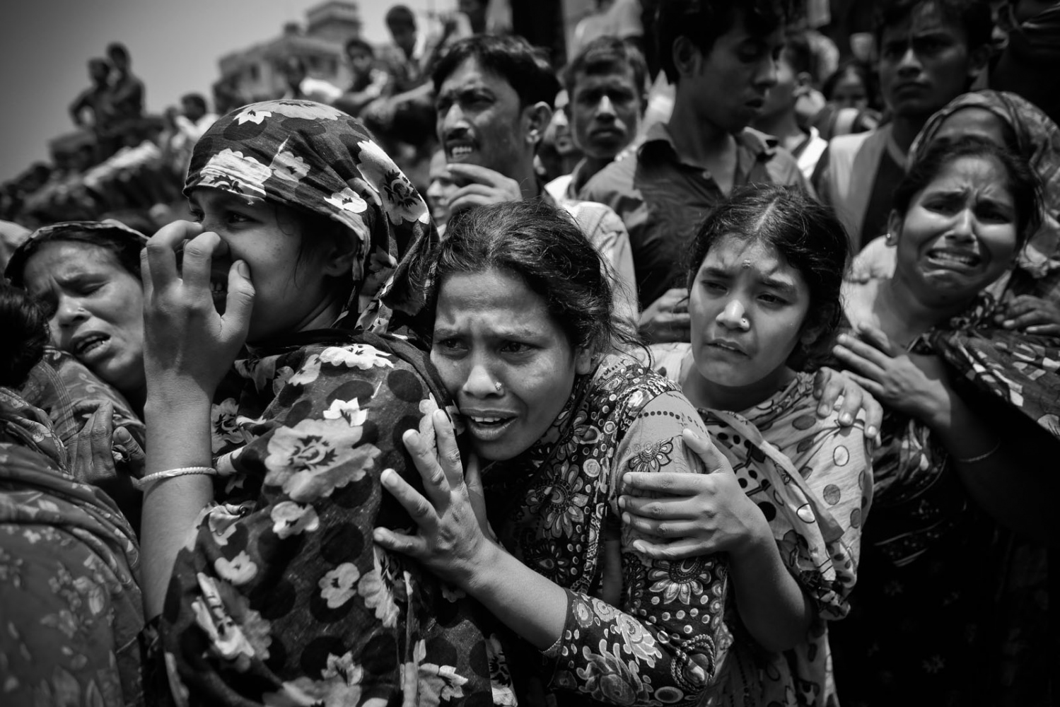 People mourn in front of the remains of their relatives, who died inside the rubble of the collapsed Rana Plaza building, in Savar, 30 km (19 miles) outside Dhaka.