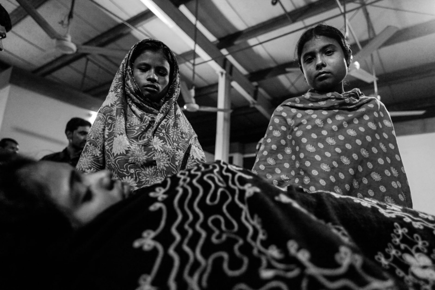 Colleagues stand beside Asma, a garment worker, who was injured in a devastating fire at Tazreen garment factory in Savar, outskirts of Dhaka. A fire swept through Tazreen Fashion factory in the Ashulia industrial belt of Dhaka, on the outskirts of Bangladesh's capital killing more than 100 people, in the country's worst ever factory blaze.