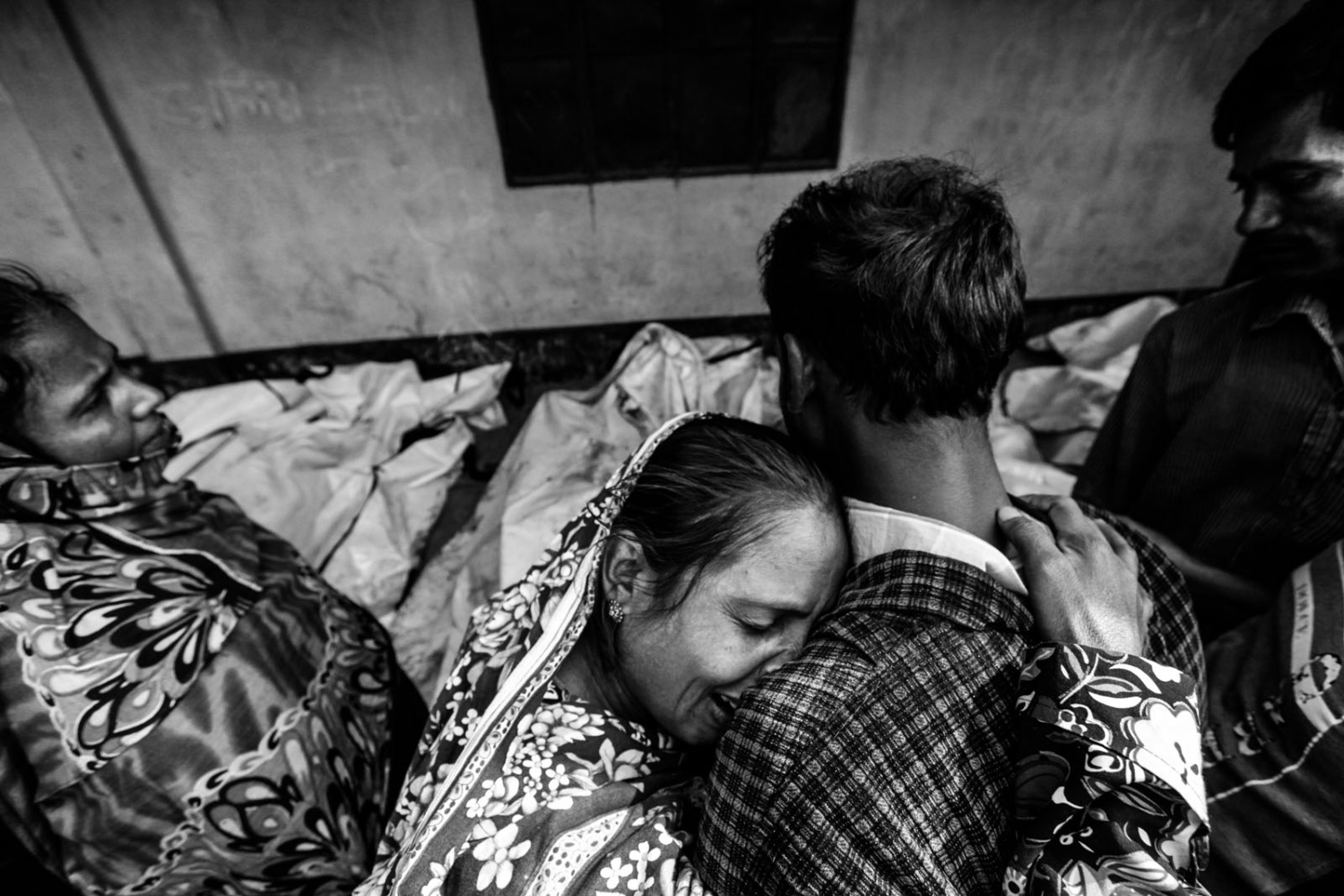 Relatives mourn the death of a garment worker after a fire occurred in a garment factory in Savar November.