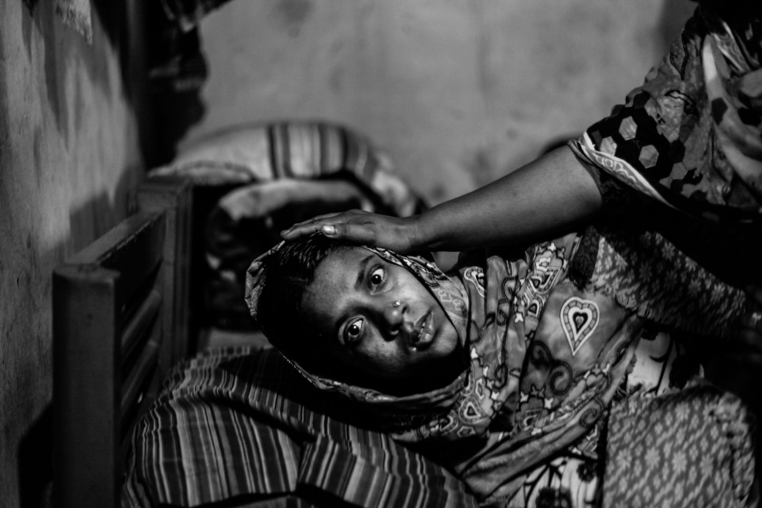 Tahera Begum, 25, who survived a devastating fire in a garment factory, lies inside her slum room in Savar. Begum, an operator of Tazreen Fashions garment factory, escaped the fire which killed more than 100 workers on November 24. According to Begum's husband, she became mentally ill and lost her memory after escaping the fire.