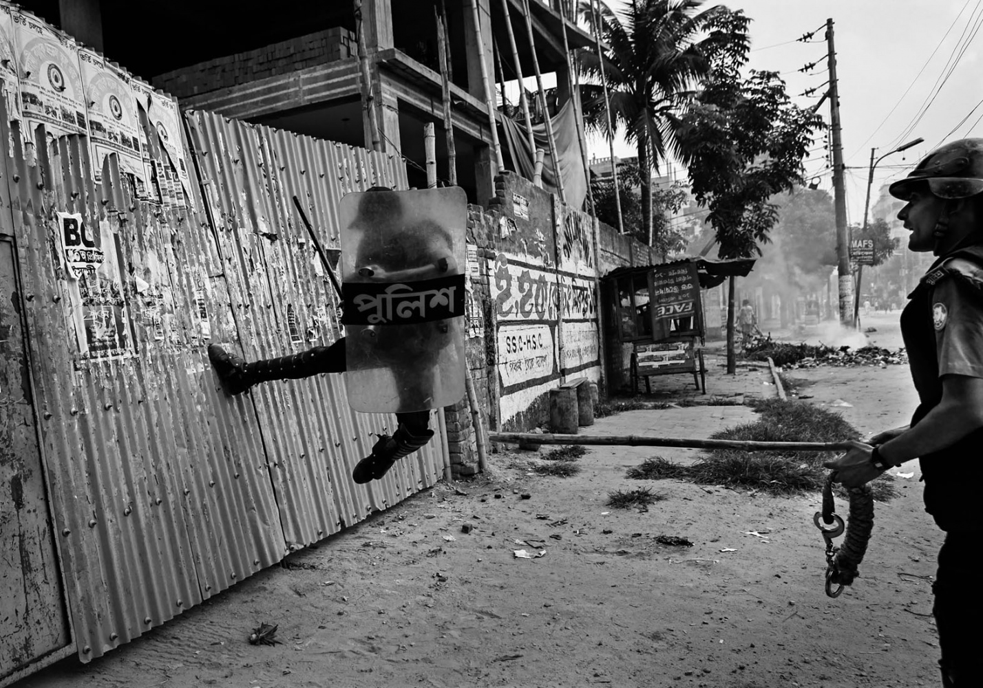 A policeman kicks the gate of a garment factory as they suspect protesters are hiding inside during a riot in Dhaka. Several hundreds of garment workers blocked the street and clashed with police demanding overtime wages and incremental increase of minimum wages to 5000 takas ($73), police said. The worker's current salary was less than 1,700 takas ($25) per month.