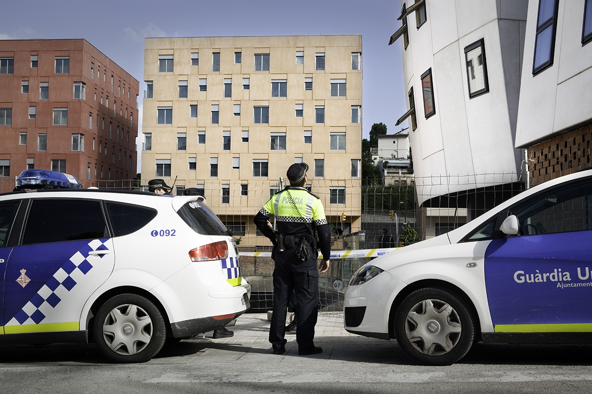 A municipal Police officer cordons the area of a new occupied building to give shelter to 12 families in the neigborhood of Torre Baró (Barcelona).