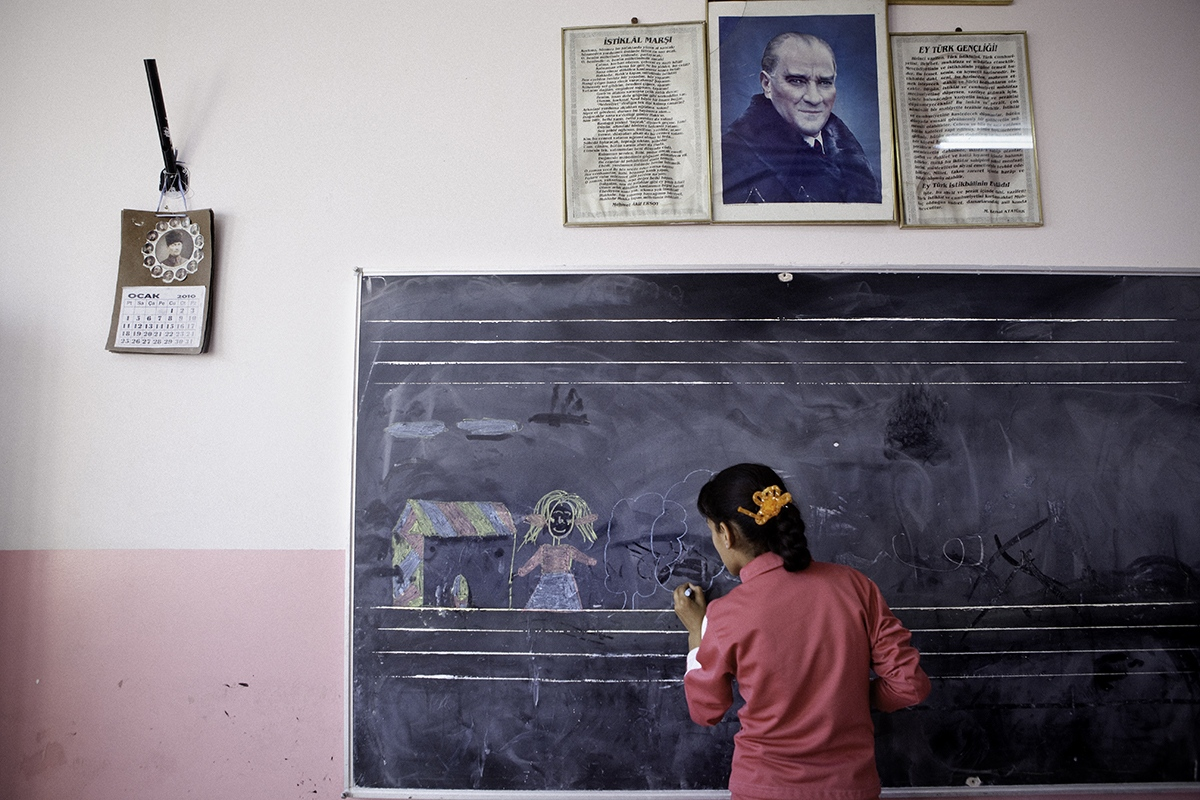 A student of Primary School in Nusaybin, near the Syrian border. A portrait of Ataturk, founder of the Republic of Turkey, chairs the classroom.