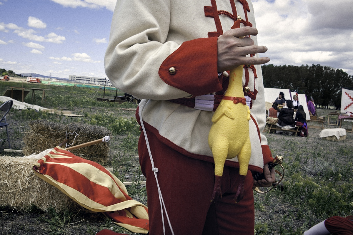 A young reenactor characterized as a hungarian soldier plays with a jelly chicken before a battle representation. Catalan flag appears defeated in the floor.