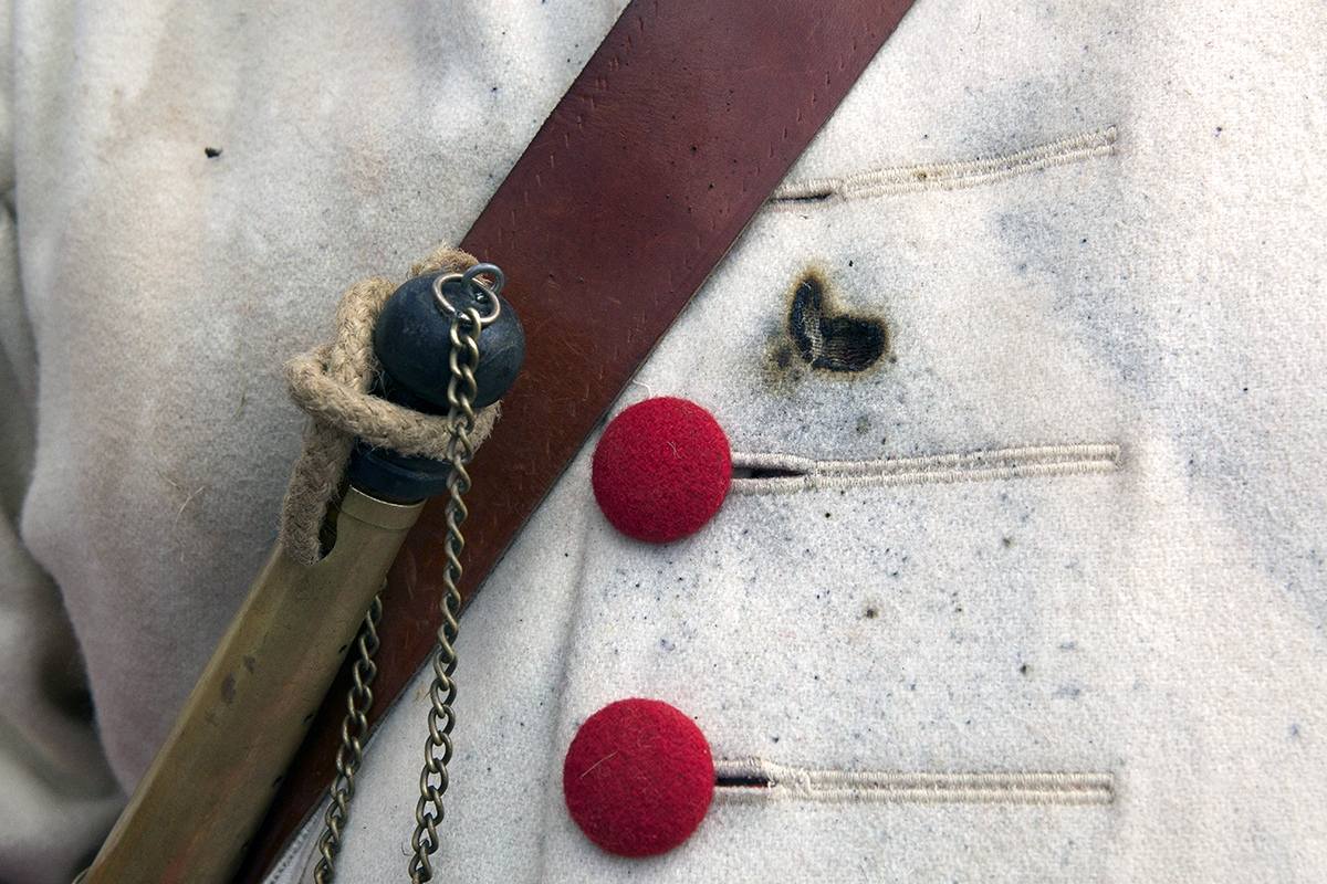 Detail of a uniform damaged by gunpowder's burns.