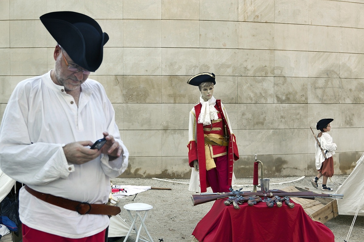 A man, a maniqui and a kid are seen dressed as a Catalan soldier of 1714.