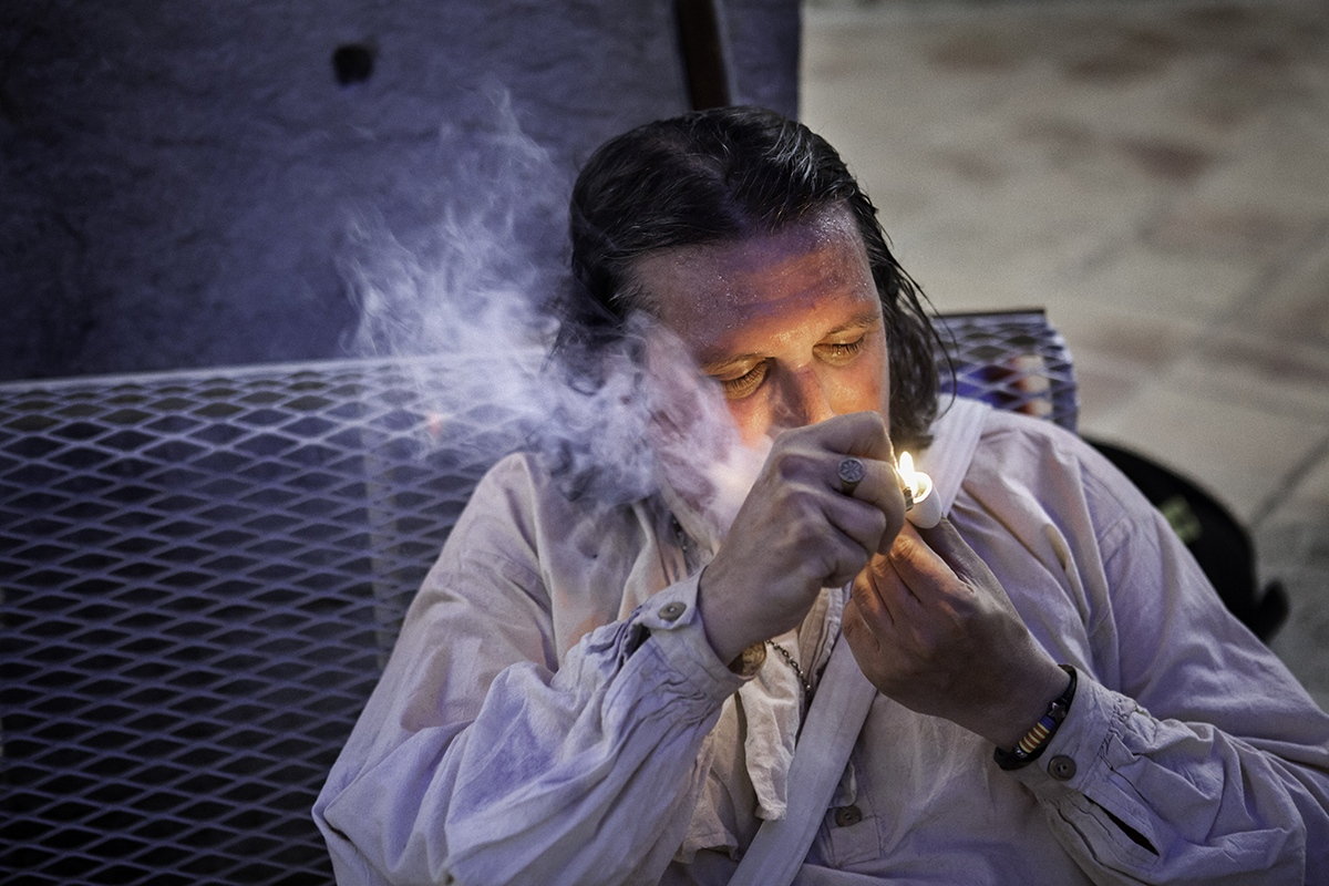 A man smokes in an old-fashioned pipe imitating a pipe of the XVIIIth century.