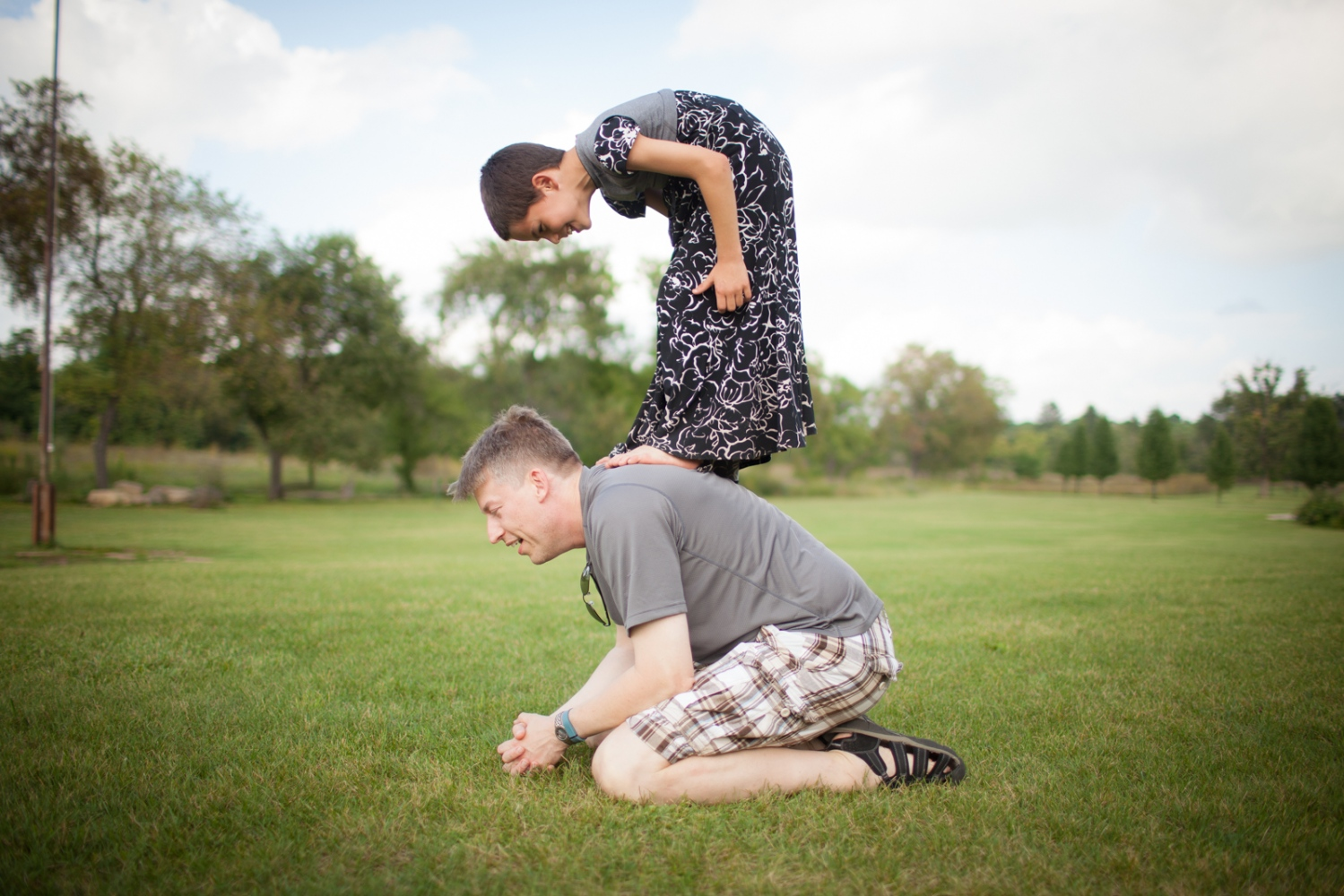 A child plays leapfrog with his father.