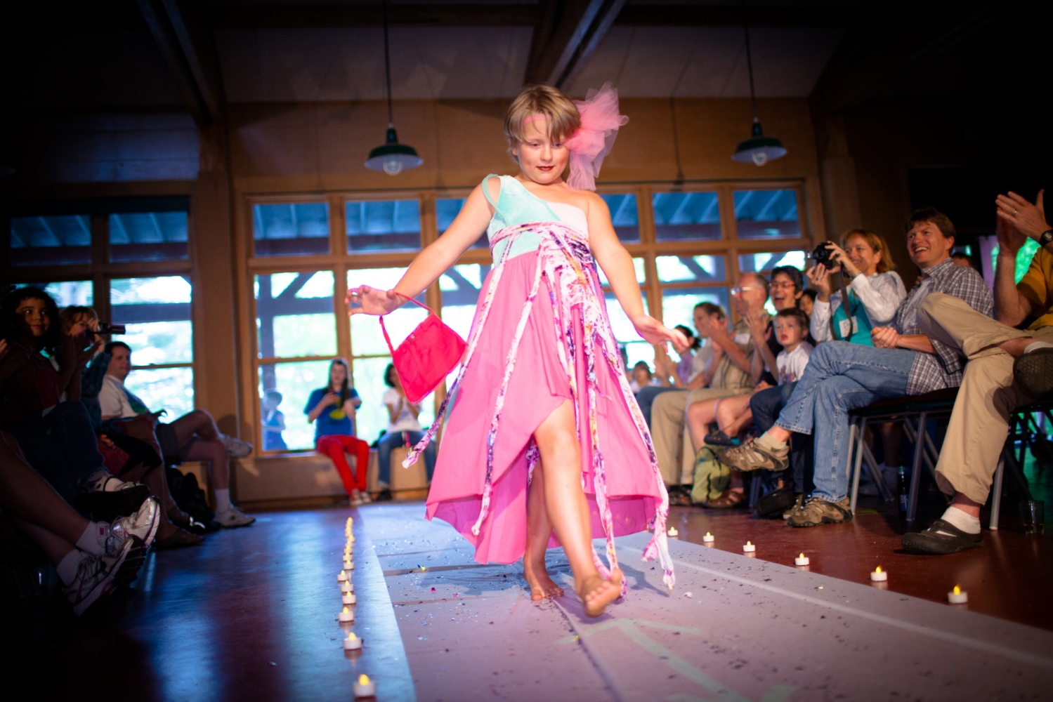 A camper walks down the runway with the enthusiastic support from the camp community.