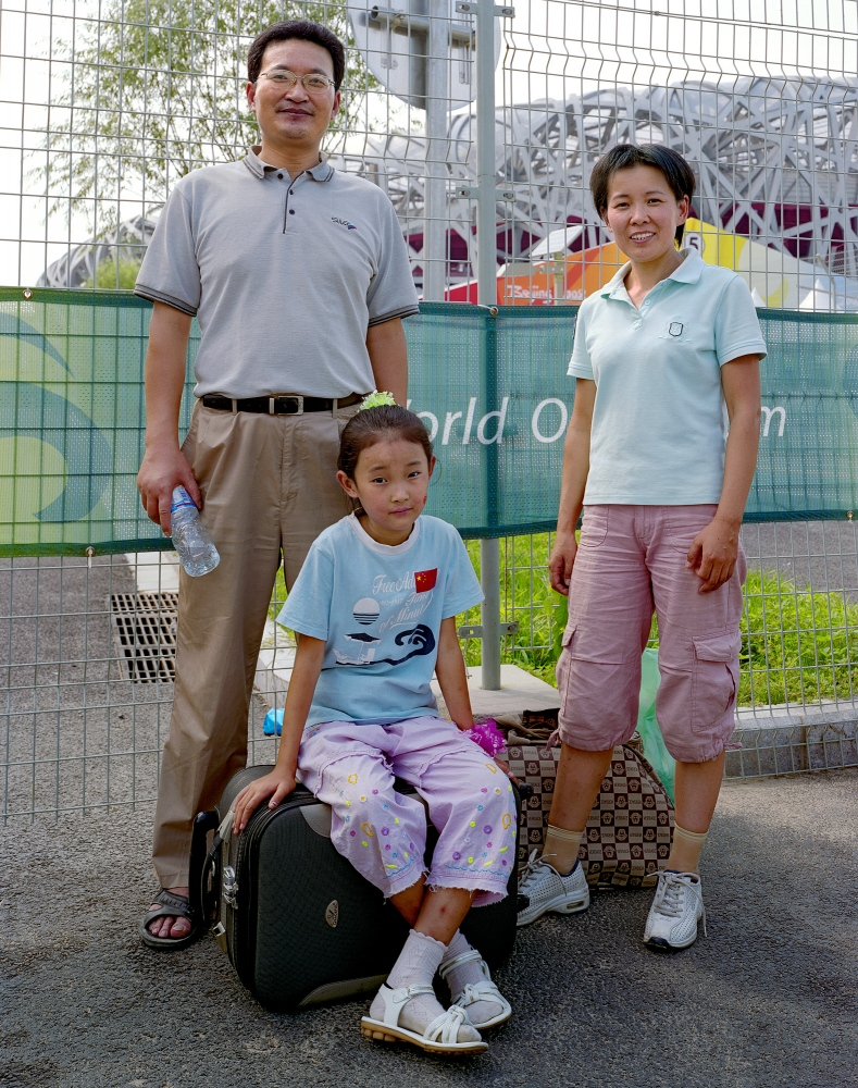 "Wang Taoping, 37, with his wife Zhang Xiaoyuan, 37 and daughter Wang Litao, 8, pass by the ""Bird Nest"" on their way home to Hebei."
