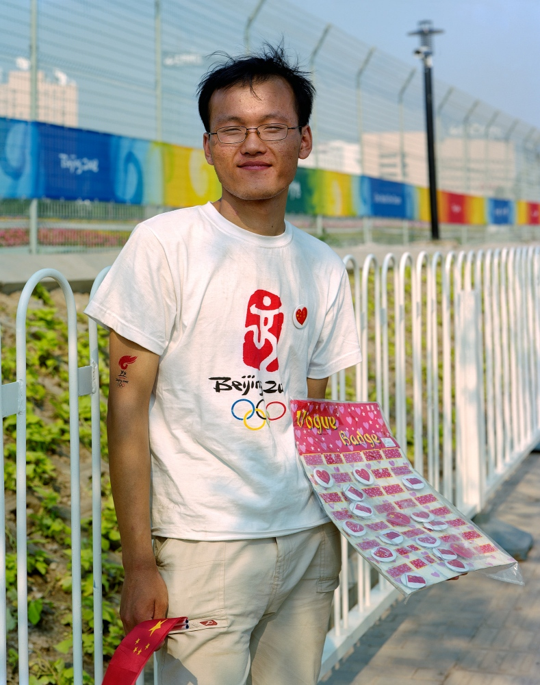 Wang Shuiying, a university student who sells souvenir stickers outside the venues, from Anhui.