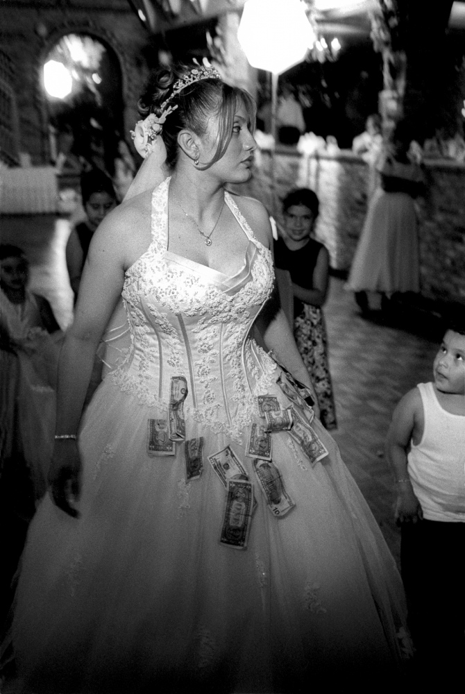 Karen collects cash during the dollar dance at her wedding. She is happy about her marriage but happier that she's about to finish school too.