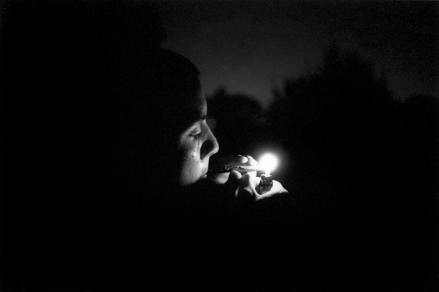Michael lights up a joint on the roof of his family's home.