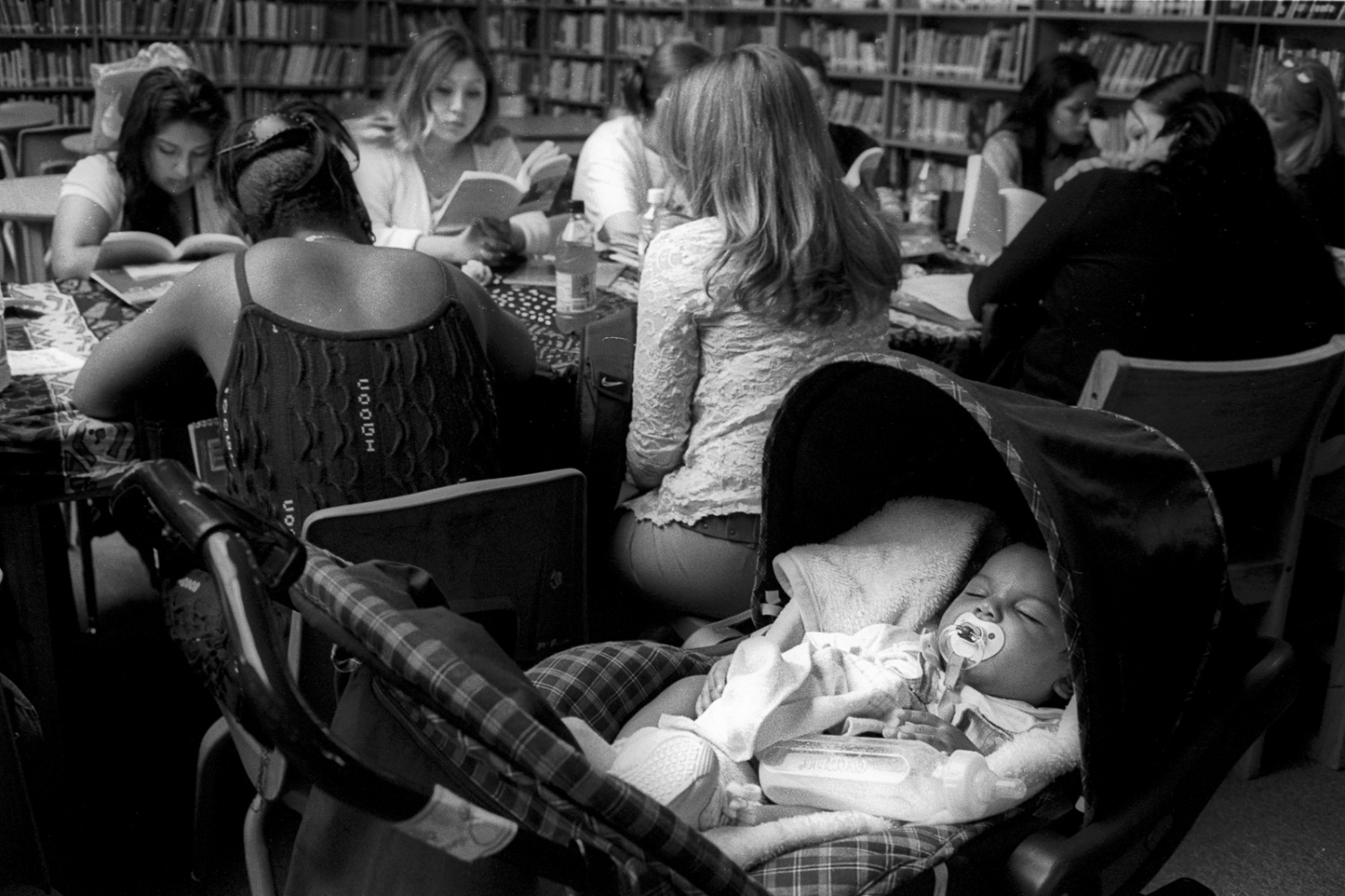 Karen's daughter naps during a girls-only writing class in the school library. School policy was that students were not supposed to bring their to class but it happened fairly often.