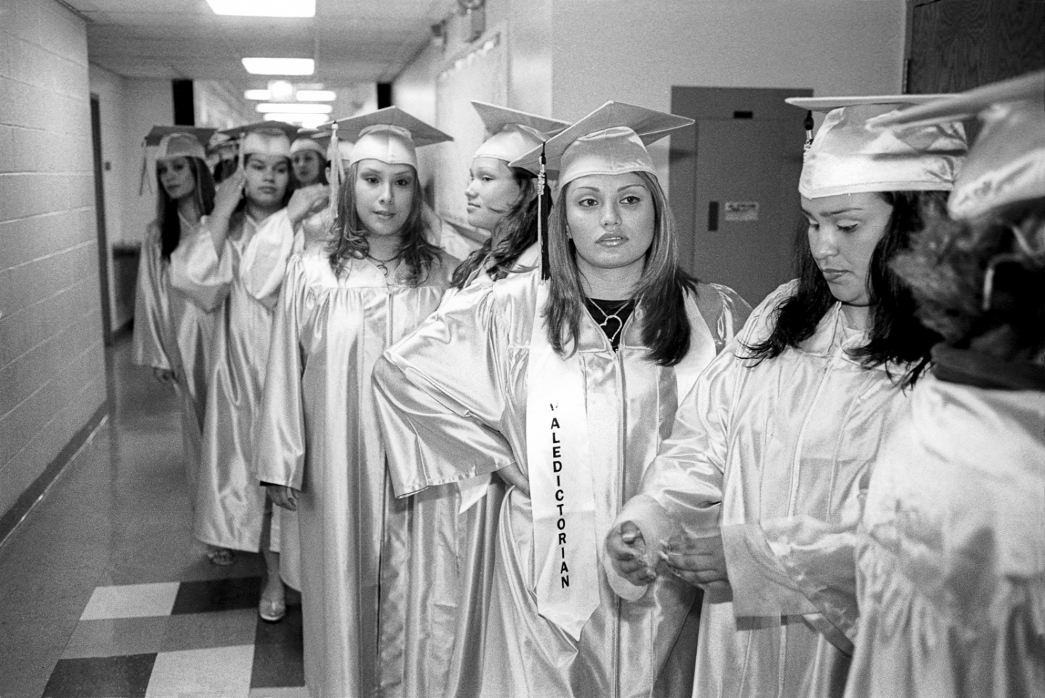 Karen waits with classmates for their graduation ceremony to start. Her marriage didn't last a year but she stayed focused on school and finished at the top of the class.