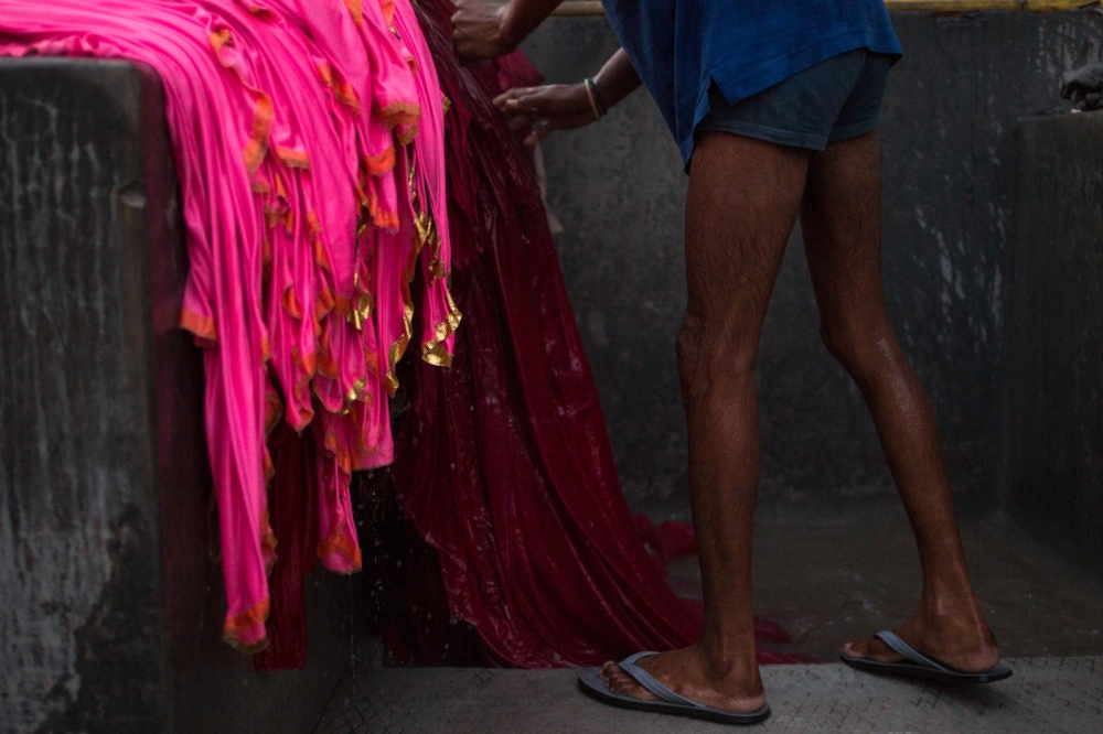 "Indian washerman Raaju Uddin, 20, stands on the edge of a stone bath used to wash clothes as he rinses fabric covers and curtains used during wedding celebrations at a dhobi ghat outdoor laundry in New Delhi on February 10, 2015. ""I make around 4,000 INR per month and we start here early morning. We have to stand in the water to clean the clothes so we heat and add the warm water."""