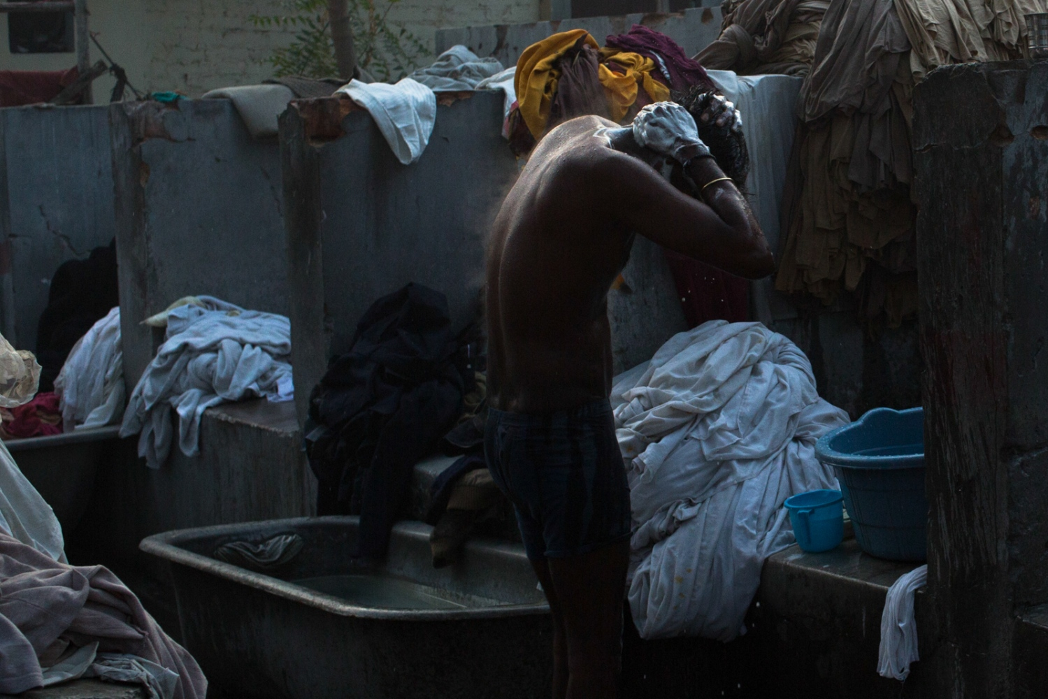 Indian washerman Dharmraj Kumar, 23, who lives and works at a dhobi ghat outdoor laundry bathes before starting work in New Delhi on February 10, 2015. With no water supply available in the homes at the ghat, residents bathe outdoors and collect water from pumps and taps for cooking and washing.