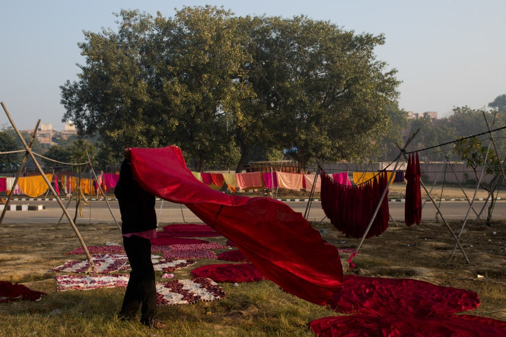 Indian washerman Parmod Chattrati, 42, lays fabric tablecloths used during wedding celebrations out to dry near a dhobi ghat outdoor laundry in New Delhi on February 10, 2015. With little space to dry clothes and fabric after washing, workers hang cleaned laundry to dry along nearby roads and set up washing lines on patches of ground between traffic lanes.