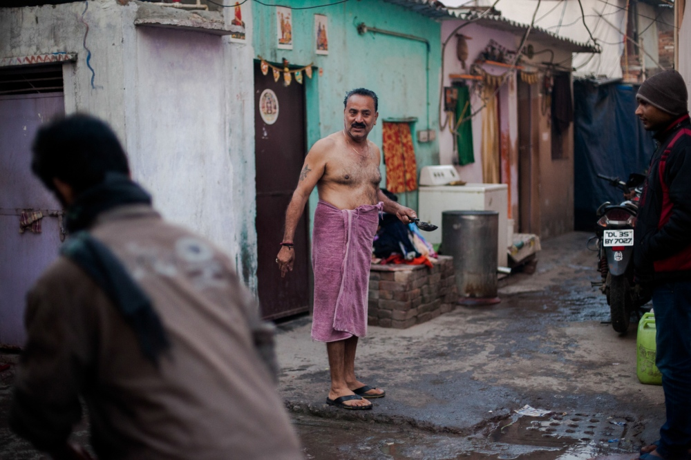 Indian washerman Prem Kumar (C), 50, talks to neighbours as he walks back to his home after performing a morning puja at a Hindu shrine in a dhobi ghat outdoor laundry where he lives wih his family in New Delhi on February 12, 2015. Prem leaves incense, carried in a small pan, burning at the shrine as an offering every morning before bathing and then starting work.