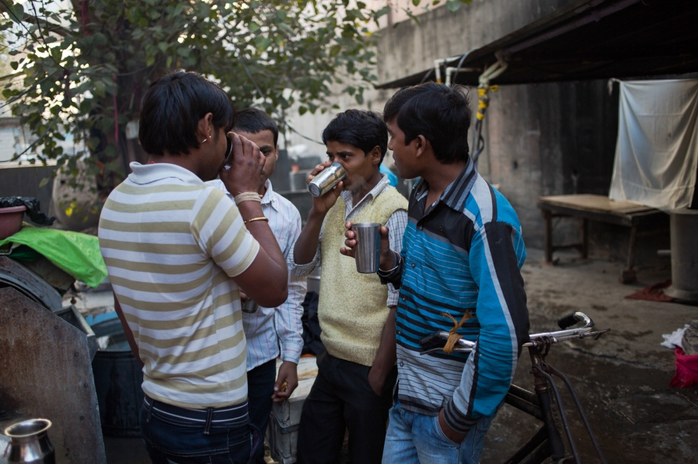 Indian washermen Bula Kumar (L), 23, Rupesh Kumar (2L), 22, Parmod Kumar (2R), 22, and Pardeep Kumar (L), 24, and who are not related, talk and drink chai before starting work at a dhobi ghat outdoor laundry in New Delhi on February 12, 2015. None of them attended school, and work for a family who wash towels and bedding for hotels, beauty parlours and spas in the city, unloading spin-driers, collecting and delivering laundry, and using bicycle-carts to transport and hang items to dry along the roadside near the ghat area.