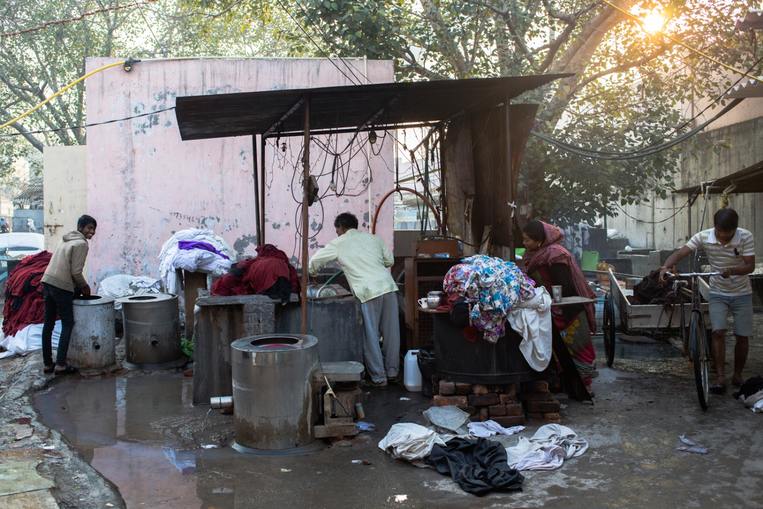 "Indian washerman Om Prakash (C), 49, and his wife Sunita (2R), 39, talk with their employees Rohit Kumar (L), 16, and Bula Kumar (R), 23, as they work to wash and dry towels used at a spa in the city at a dhobi ghat outdoor laundry in New Delhi on February 12, 2015. Together the couple run a business providing laundry services for hotels, beauty parlours and spas in the city, collecting and delivering towels and bedding. Om says, ""I have been working here for 28 years, and I have been married to my wife for 26. She is my Agra, my Taj Mahal, my sunrise, my queen."""
