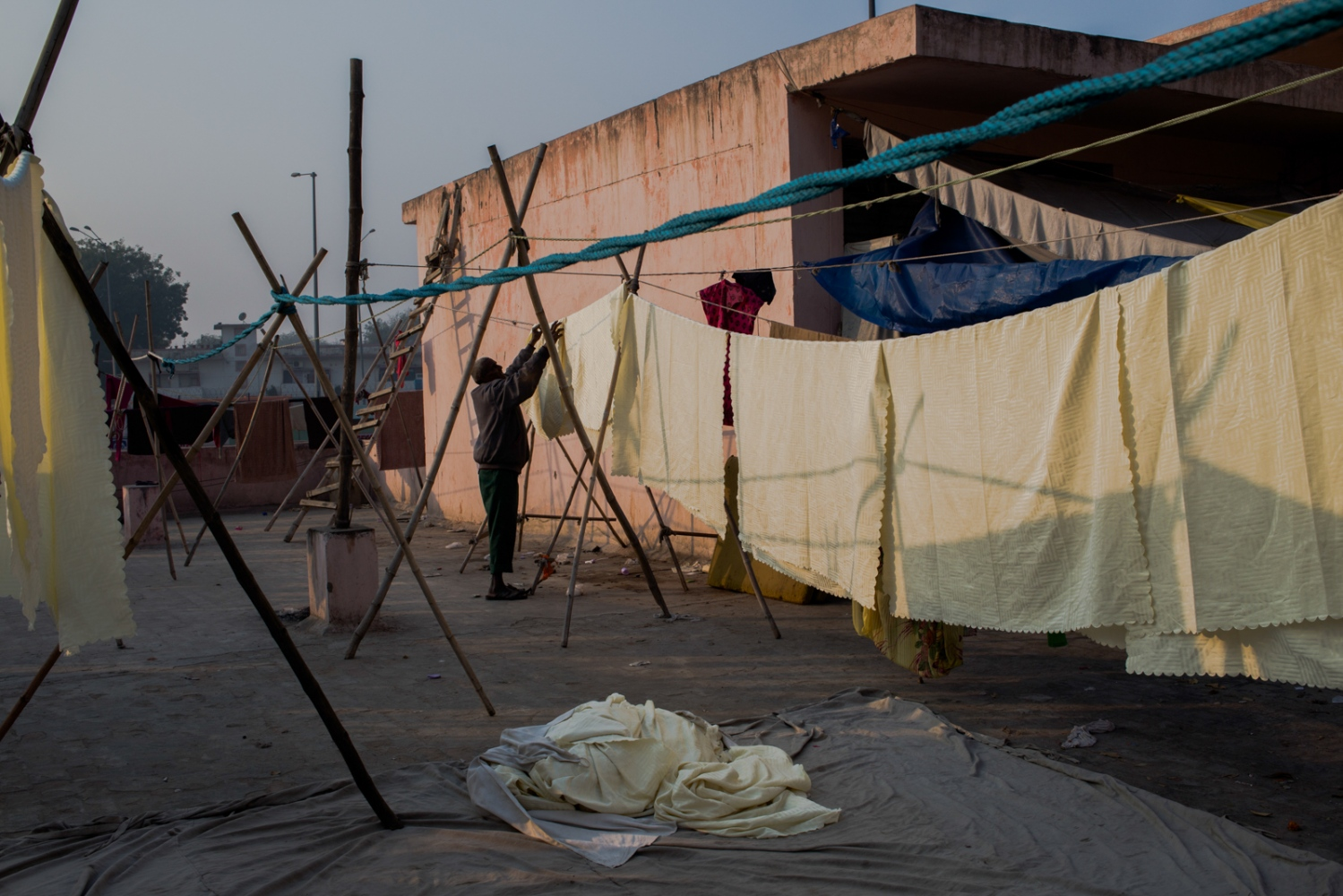 "Indian washerman Sahamuddin, 52, and who goes by one name, hangs sheets to dry before sharing chai with other workers at a dhobi ghat outdoor laundry in New Delhi on February 12, 2015. ""We don't make the same money every day, it changes with whatever work we get, but we only need five rupees for chapati (bread)."""