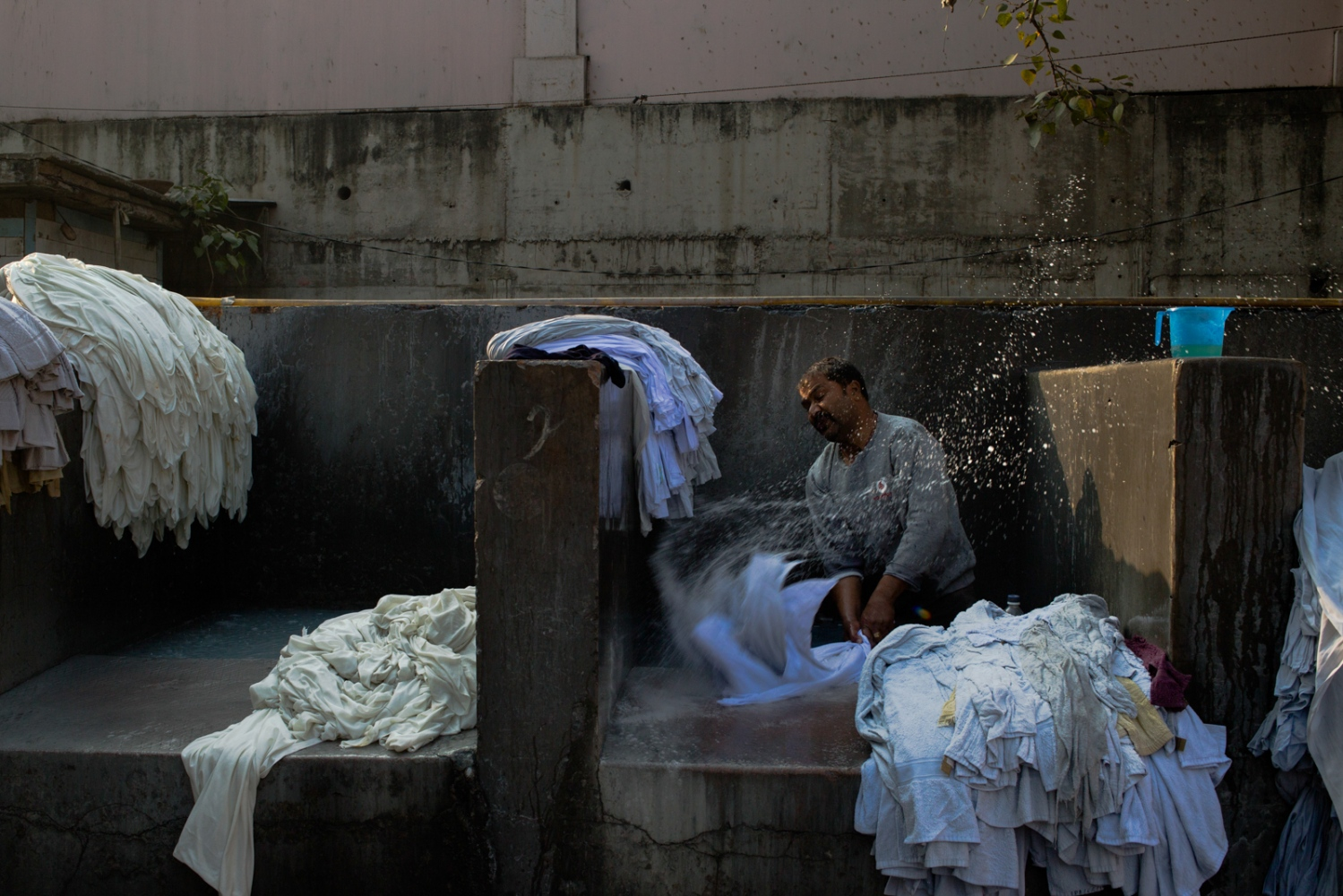 Indian washerman Babu Jan, 42, stands in stone bath as he beats items of clothing to clean and rinse them at a dhobi ghat outdoor laundry where he lives with his family in New Delhi on February 12, 2015.