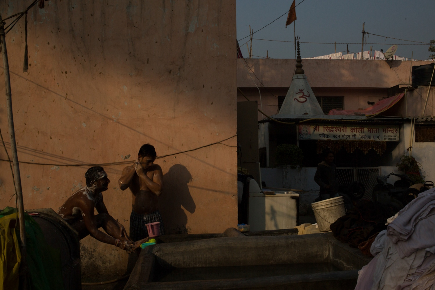 "Indian washerman Surej Kumar (L), 20, bathes at a dhobi ghat outdoor laundry where he lives in New Delhi on February 12, 2015. Surej and his father work as a washermen at the ghat in the early morning, and Surej then leaves for work at a sari shop in the city's Lagpat Nagar market, where he sells outfits for weddings. ""The money is better there than here - here the wages every month are smaller so I work outside as well."""