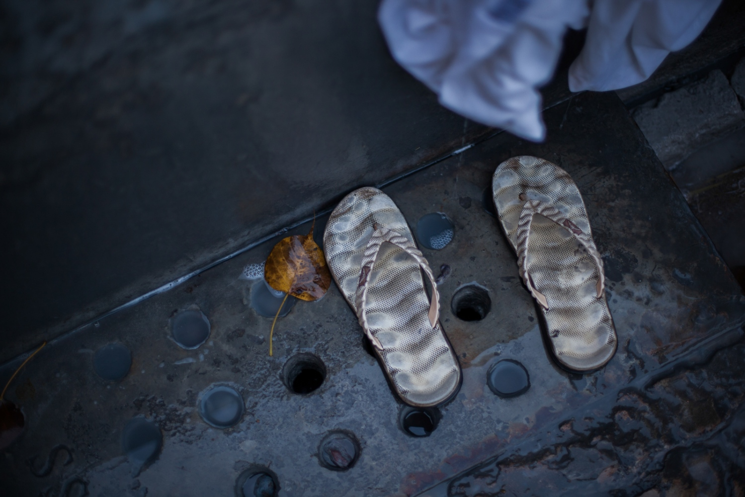 "Flip-flops belonging to Indian washerman Yogesh Kumar, 35, lie next to a stone bath as he washes clothes at a dhobi ghat outdoor laundry where he lives with his family in New Delhi on February 17, 2015. Yogesh has worked at the ghat for 15 years and says. ""It's hard. The water gets cold and the clothes are heavy, and we make little money."""