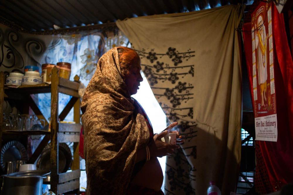 Indian resident Pushpa Binjari, 50, offers prayers over a cup of chai towards a poster bearing an image of a Hindu god before having breakfast in her home at a dhobi ghat outdoor laundry where she lives with her family in New Delhi on February 17, 2015. Pushpa performs this ritual every morning before starting chores and preparing meals for her son and his wife, with whom she lives following the death of her husband.