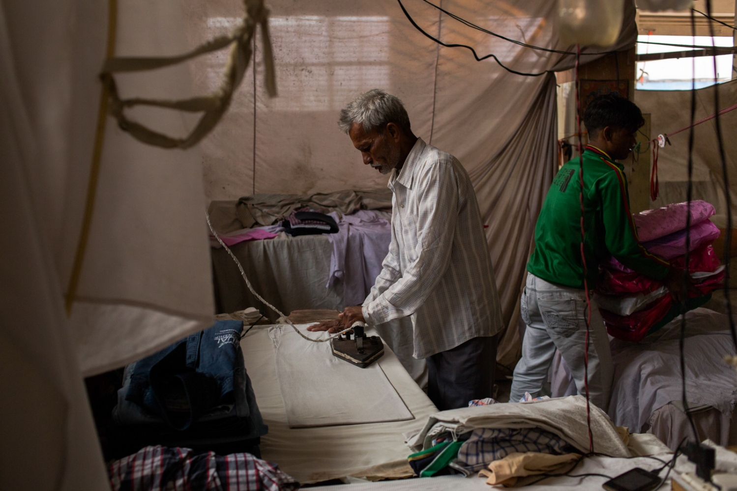 Indian washerman Abdullah Hassan (C), 54, irons an item of clothing as another worker takes freshly-ironed and packed clothes to be delivered to customers at a dhobi ghat outdoor laundry in New Delhi on February 17, 2015.