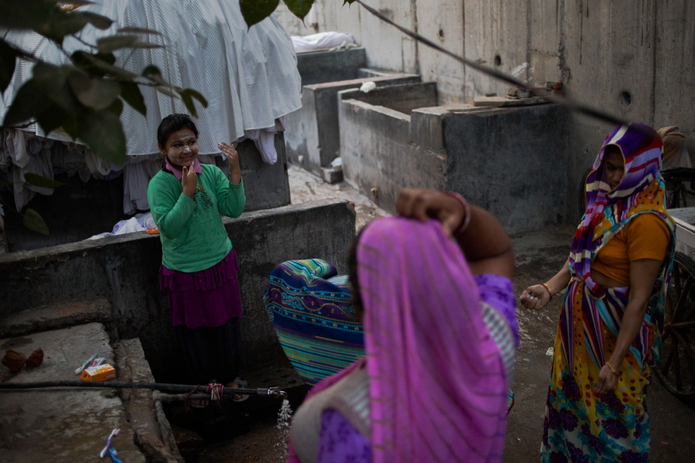 Indian schoolgirl Kushi Kumar, 8, and whose father works as a washerman, washes her face at a communal tap at the dhobi ghat outdoor laundry where she lives with her family in New Delhi on February 18, 2015. With no water supply available in the homes at the ghat, residents bathe outdoors and collect water from pumps and taps for cooking and washing.