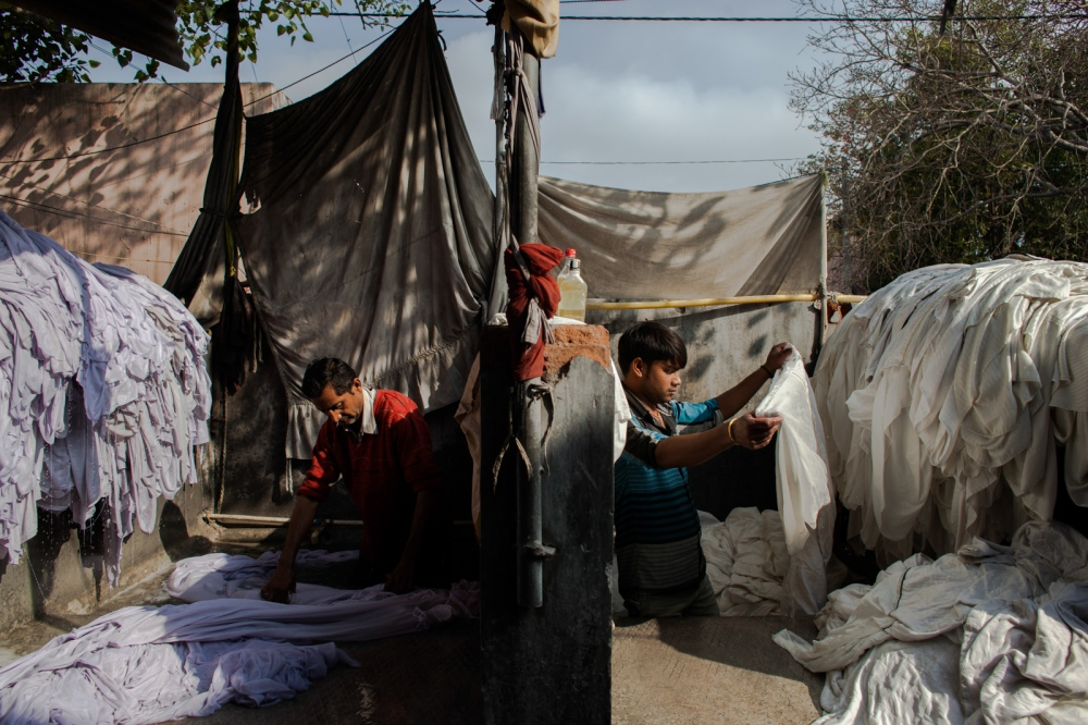 "Indian washerman Yogesh Kumar, 35, washes clothes at a dhobi ghat outdoor laundry where he lives with his family in New Delhi on February 17, 2015. Yogesh has worked at the ghat for 15 years and says, ""It's hard. The water gets cold and the clothes are heavy, and we make little money."""