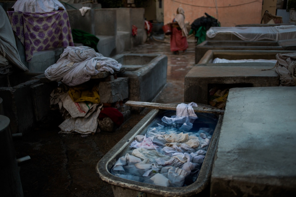 Fabric soaks in a whitening solution used to bleach stains at a dhobi ghat outdoor laundry in the Indian capital New Delhi on March 18, 2015.