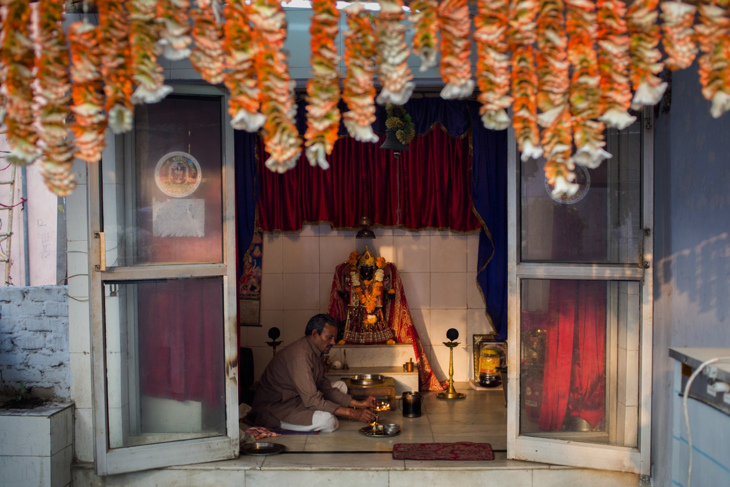 "Indian Hindu priest Pandit Madan Mohan Mishra, 42, offers a daily morning prayer during a puja ceremony at the Kalimata Mandir temple at a dhobi ghat outdoor laundry where he lives with his family in New Delhi on March 18, 2015. ""Kali is my god. The whole world is under Kali. I am not a rich man, but I am the priest here in this area. I do this puja every morning at 7am and offer prayers for my family and for all people here."" Mishra offers prasad, or sweets used as temple offerings, that he has blessed to washermen working at the ghat after each morning ceremony."