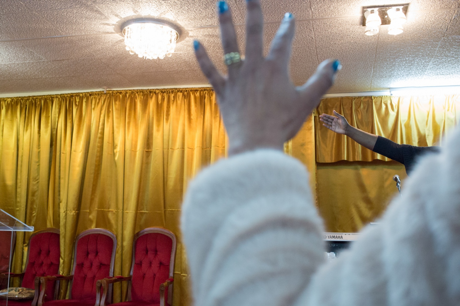Prayers in an African Christian church in Bagnollet. The Afro-French community frequents often Protestant mixed with African rituals, having the Gospel as a religious rhythm. Bobigny, Ile de France, France, 2015
