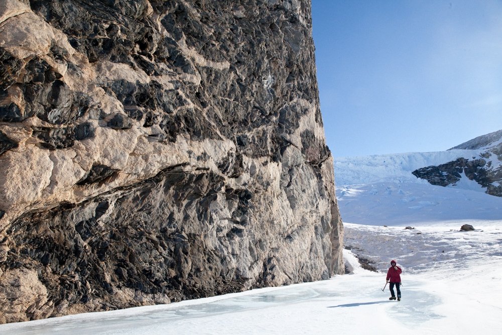 Dr. Yakymchuck traverses a frozen melt-pool underneath some highly metamorphosed 'migmatite' rock. Sampling and mapping these outcrops was the primary goal of the science expedition.