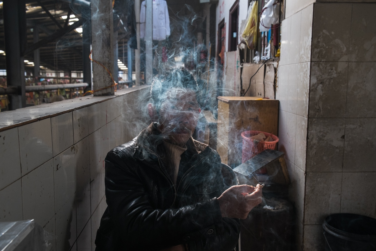 A bathroom attendant at a market smokes a cigarette, Kunming, February 2015.