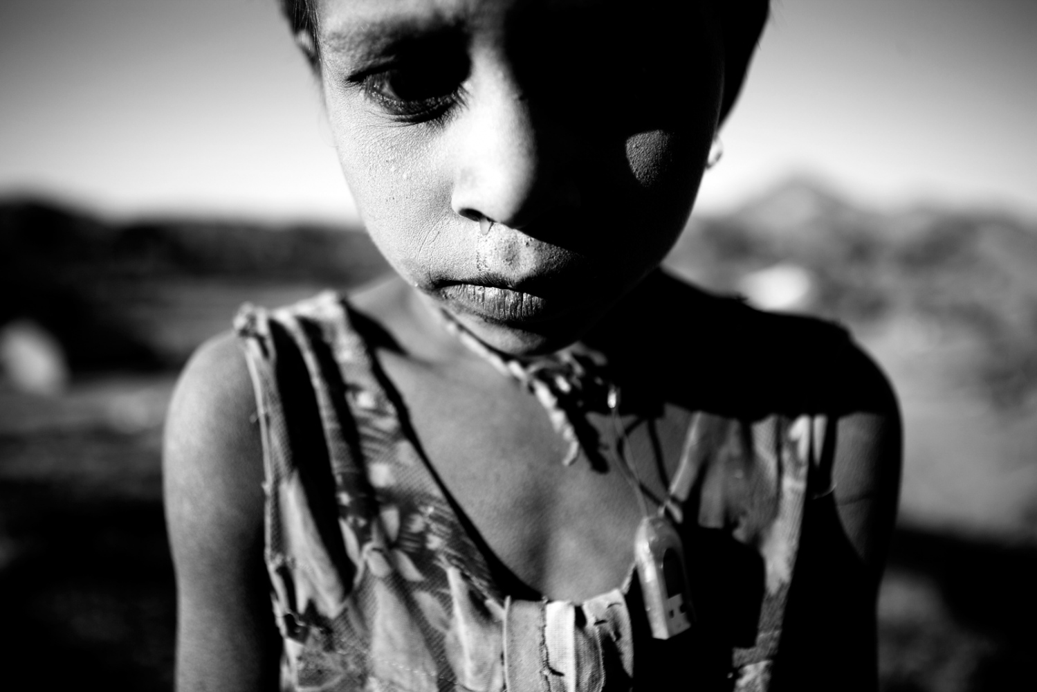 Palu, Rajasthan 2012 While interviewing the widow Hansa Bai in a tini village with no electricity far off road we met little Palu. She is one of three daughters from the poorest family there. Her eyes are amber and her hair has blond streaks due to malnutriton. She wore a broken USB around her neck.