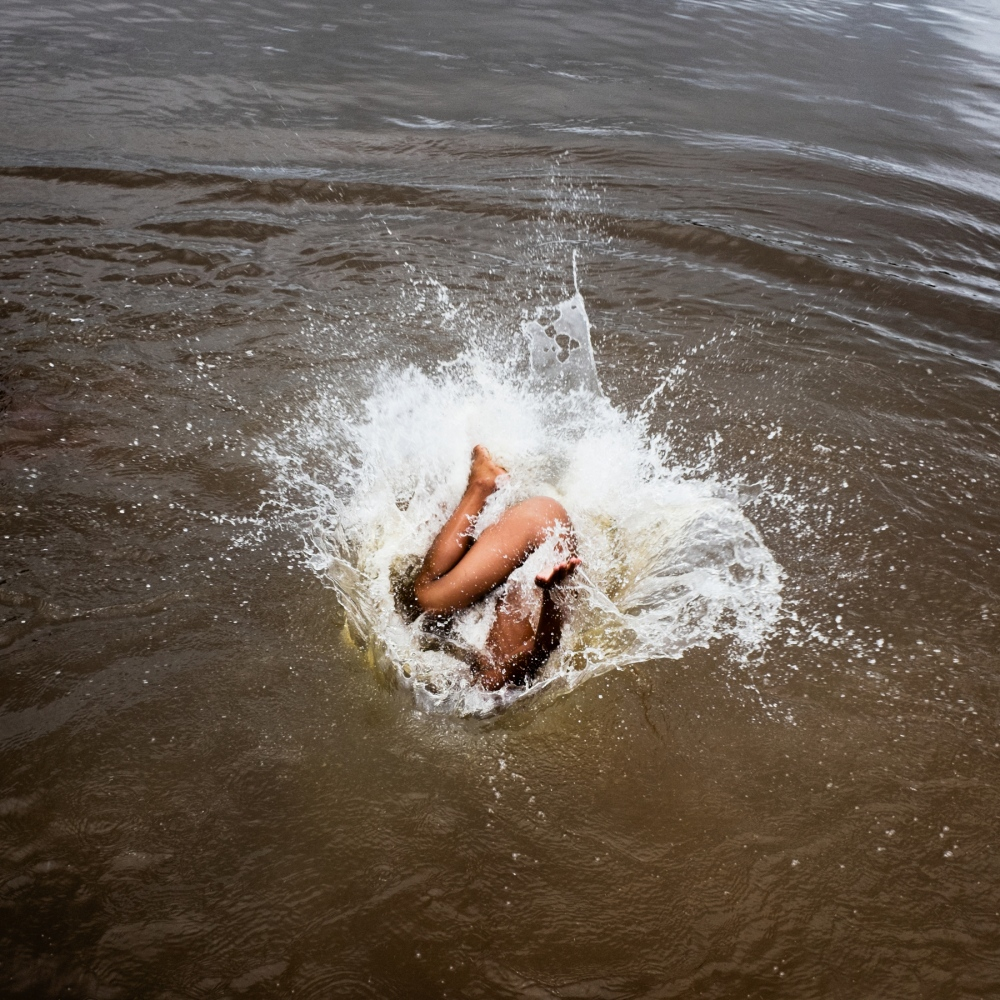 "2014. A child from the Xikrin village of ""Pot crô"" jumps into the Rio Bacaja, its name meaning ""the water that runs in river is the same as the blood that flows through our veins.""  The Bacaja, a tributary of the Xingu River which the people depend upon for fish and transportation, will severely dry up after the dam is completed."